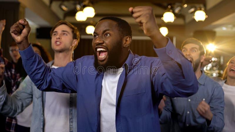 Эмоциональный африканский человек с друзьями за победой ликования, успехом проекта стоковая фотография
