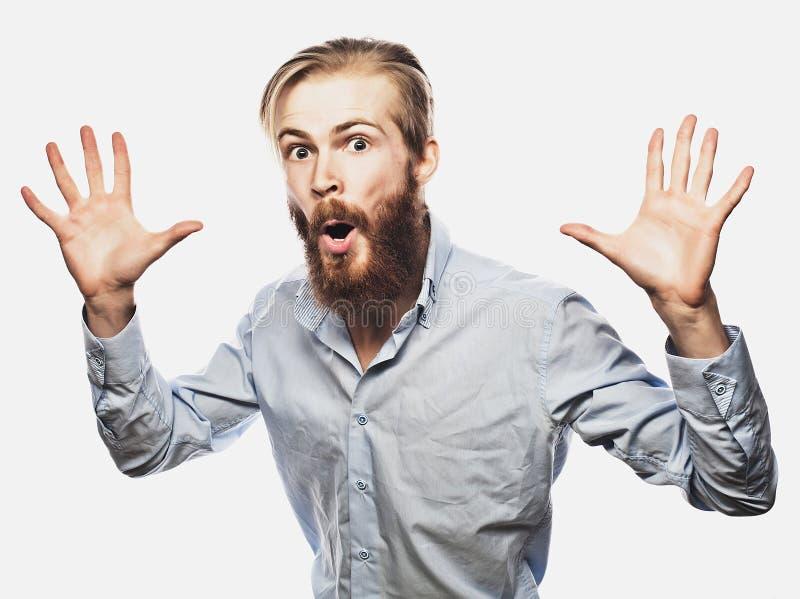 Эмоциональный бизнесмен вытягивает его руки врозь, выражающ сюрприз и разочарование владение домашнего ключа принципиальной схемы стоковое фото rf