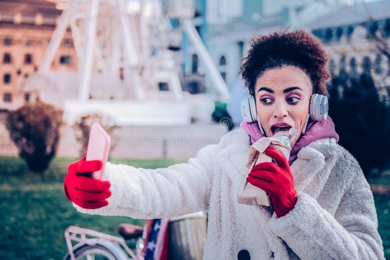 Эмоциональный женский человек принимая фото пока ел стоковые изображения rf