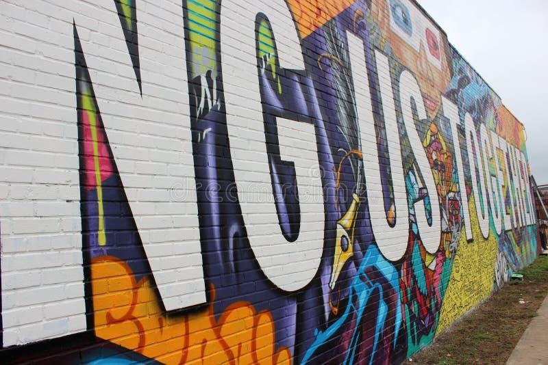 """Эмоциональный пунш в стене граффити которая читает """"эти стены приносит нас совместно """", Остин, Техас, 2018 стоковая фотография"""