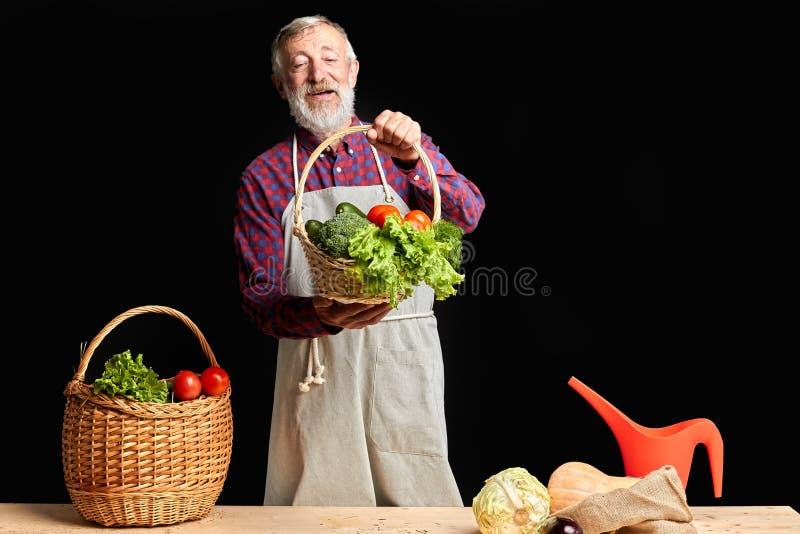 Эмоциональный старший greengrocer демонстрируя свежие сочные овощи в корзинах стоковые фото