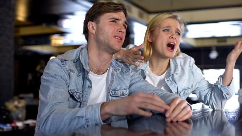 2 эмоциональных друз наблюдая игру совместно, осадили со спортом результата спички стоковая фотография