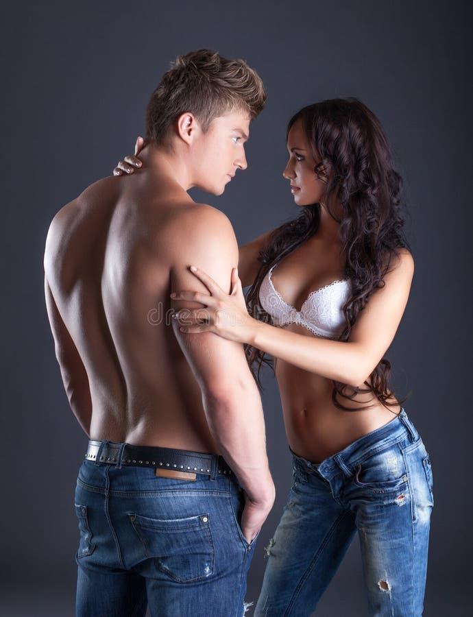 Эмоциональные молодые пары представляя в модных джинсах стоковые изображения