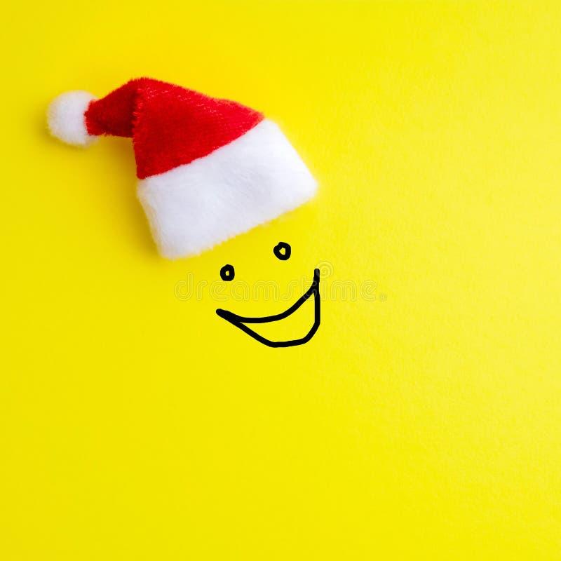 Эмоция смеясь стороны покрашенной дальше на желтой предпосылке под красной шляпой Санта Клауса Концепция счастливых Нового Года и стоковое изображение rf