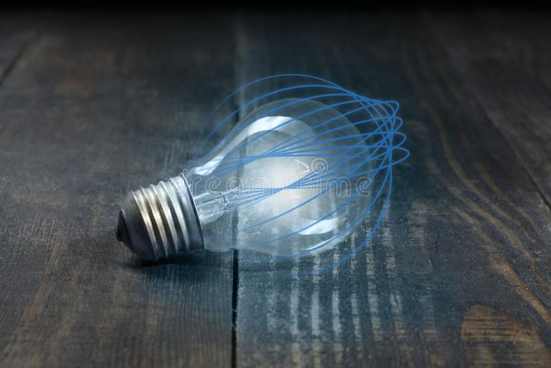 Энергетические технологии электрической лампочки которая изолирована от голубых изогнутых линий и красоты деревянных волокон доск стоковые изображения