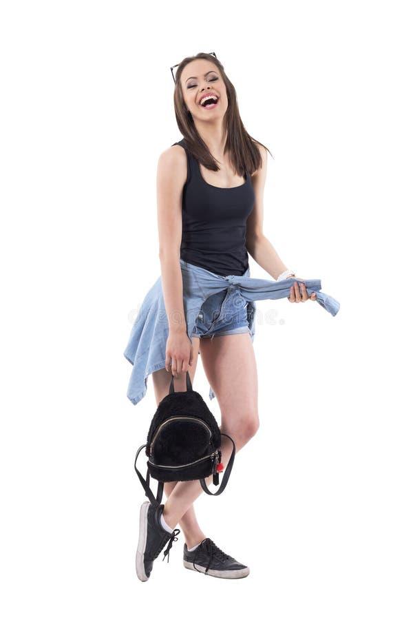 Энергичная здоровая тысячелетняя молодая стильная девушка с пушистой сумкой смеясь heartily и смотря камеру стоковая фотография