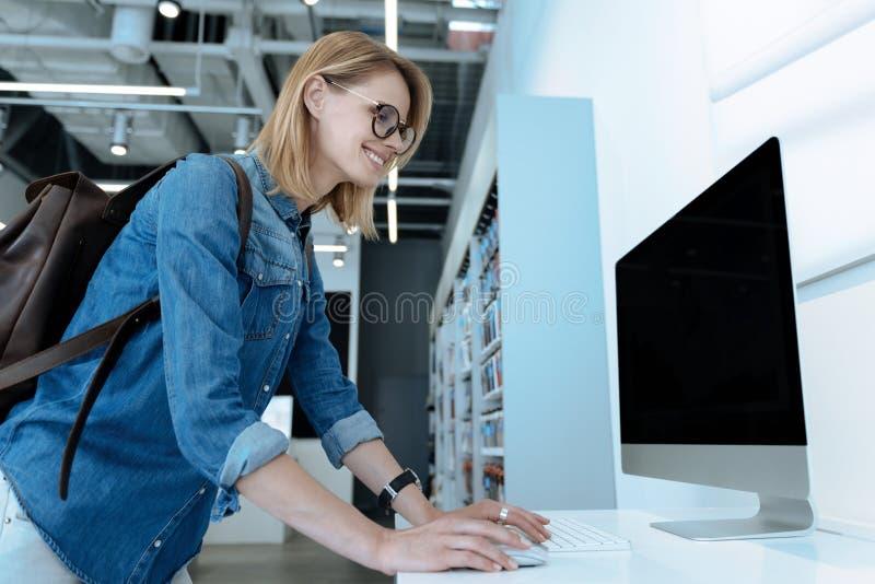 Энигматичная блондинка используя современный компьютер стоковые фотографии rf