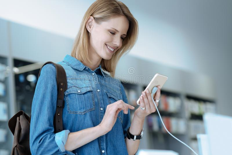 Энигматичная блондинка тот покупая smartphone стоковые фото