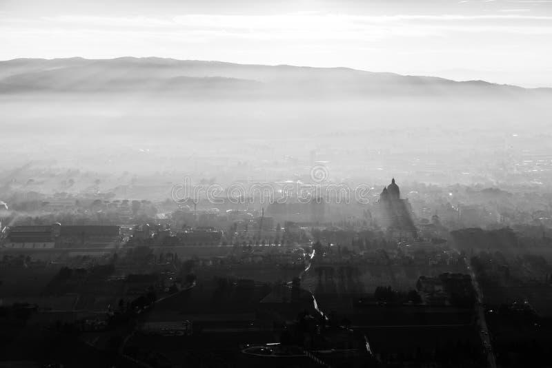 Эпичное, вид с воздуха городка Assisi Angeli degli Santa Maria, с солнцем приходя вниз и проектируя sunrays, и стоковая фотография rf