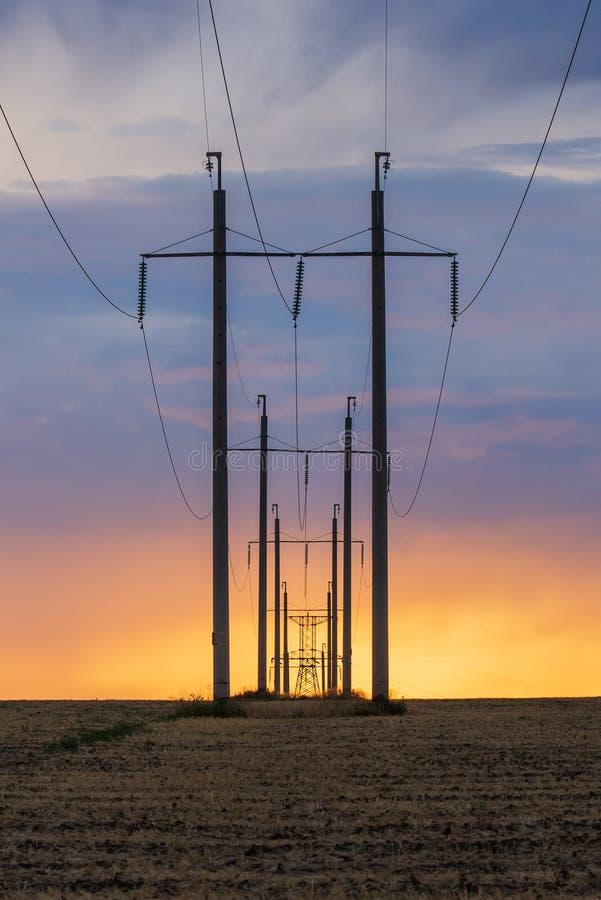 Эпичный заход солнца с сельским ландшафтом с линией высокого напряжения стоковое фото