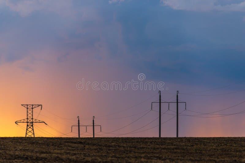 Эпичный заход солнца с сельским ландшафтом с линией высокого напряжения стоковая фотография