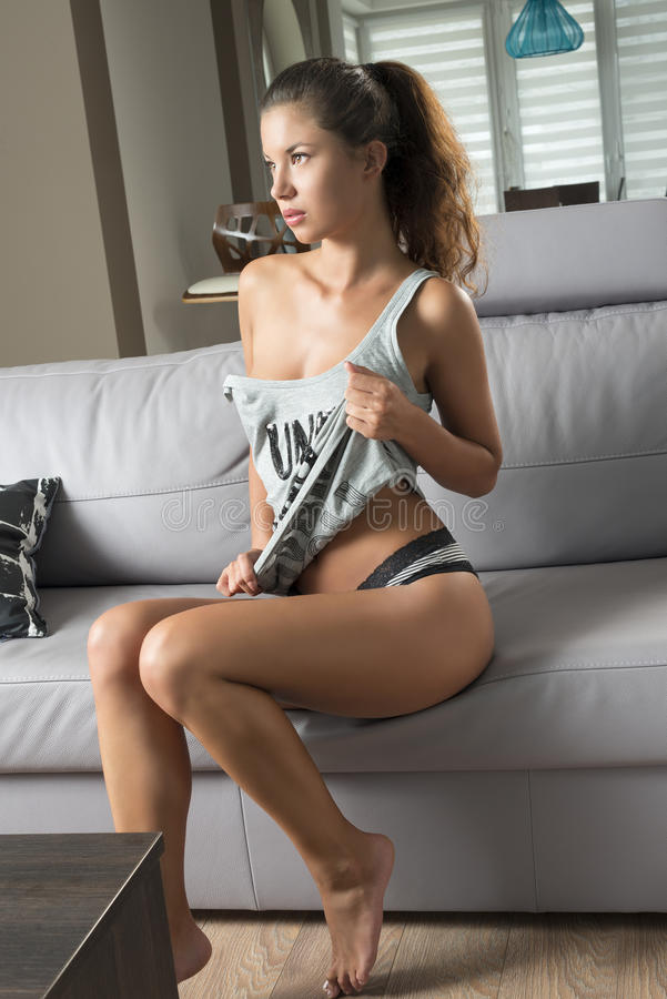 Эротичная девушка сидя на софе стоковое изображение