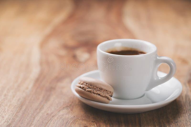 Эспрессо с macaron на деревянной таблице стоковое изображение rf