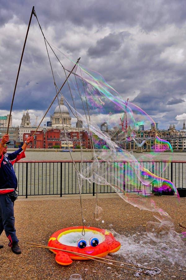 Эстрадный артист улицы Лондона создает мега пузыри стоковая фотография
