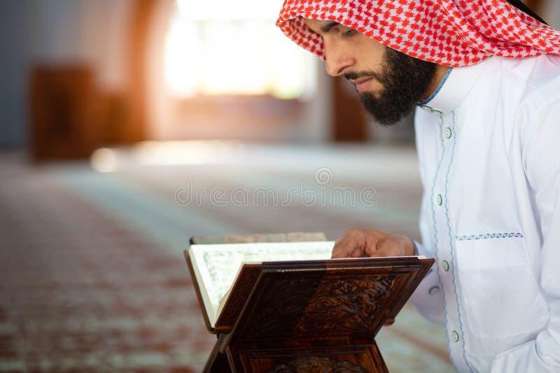 Этнический человек читая Koran и молить в мечети стоковые фото