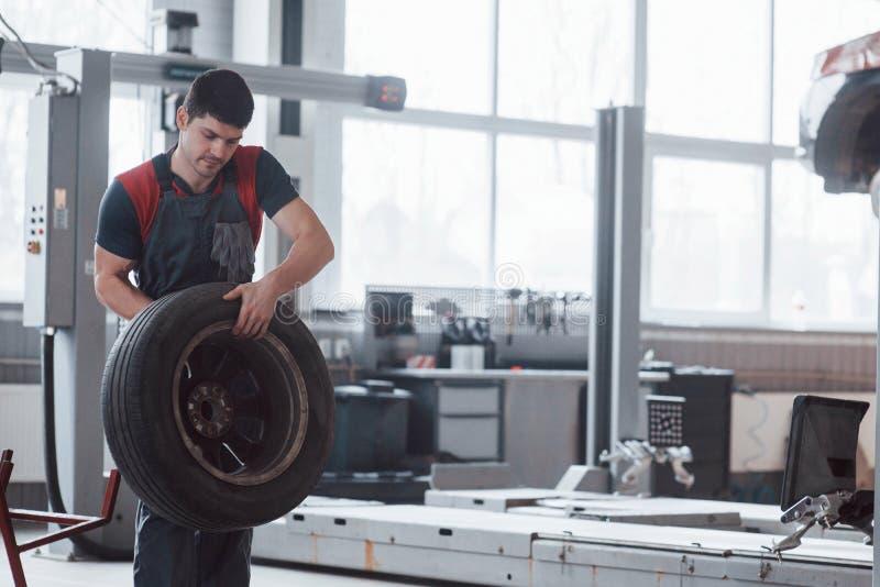 Это не так уж сложно Механик с шиной в ремонтном гараже Замена зимних и летних шин стоковая фотография rf