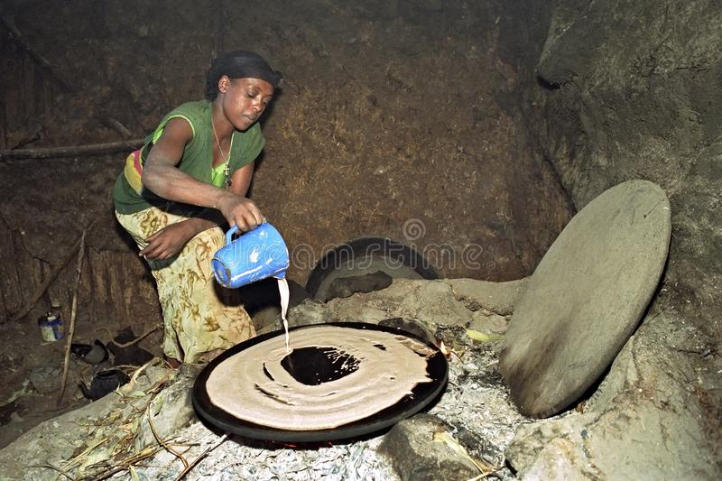 Эфиопская женщина печет injera на деревянном огне стоковые фото