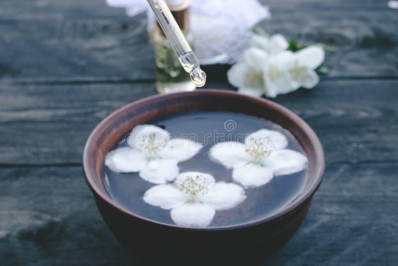 Эфирное масло и цветки жасмина на предпосылке деревянного стола стоковые фото
