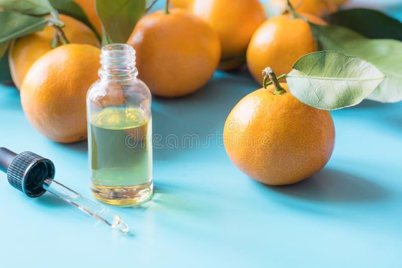 Эфирное масло оранжевого мандарина над пастельной голубой предпосылкой черная спа цветка принципиальной схемы облицовывает здоров стоковая фотография
