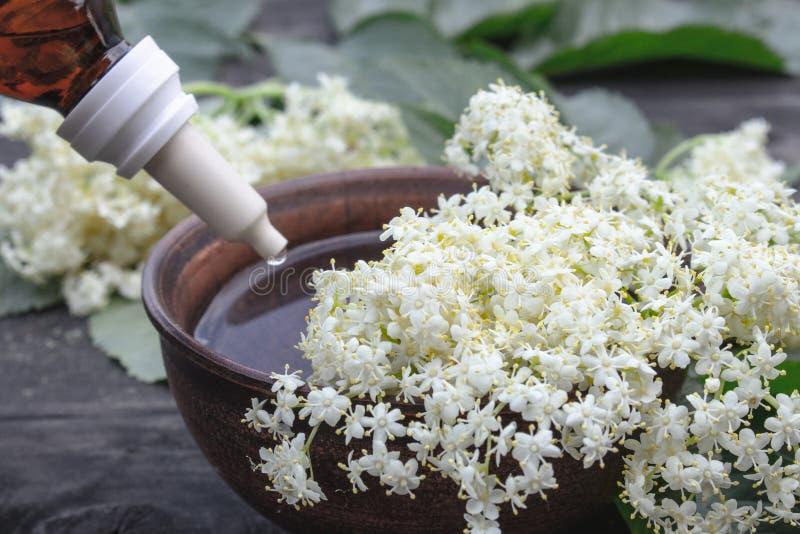 Эфирное масло Elderberry или выдержка тинктуры с цветками elderberry на деревянной предпосылке стоковые изображения