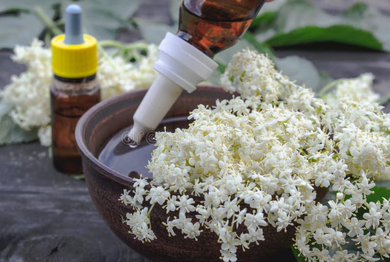 Эфирное масло Elderberry или выдержка тинктуры с цветками elderberry на деревянной предпосылке стоковое изображение