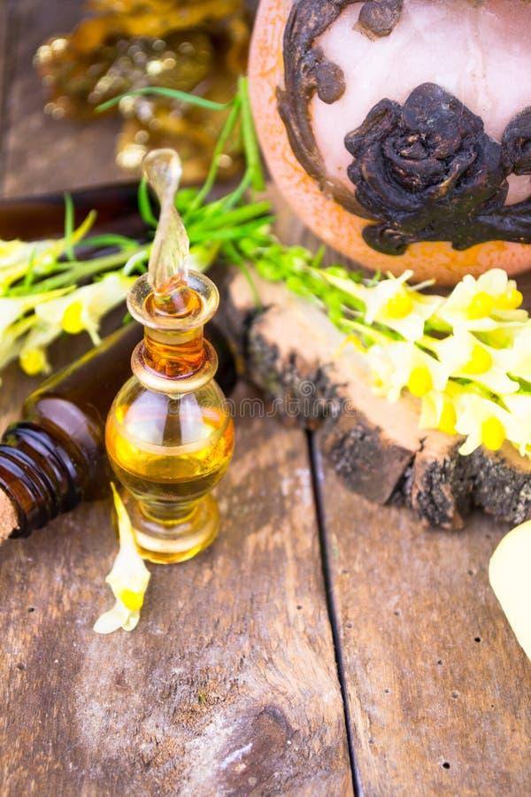 Эфирные масла и медицинские травы цветков на древесине стоковые изображения