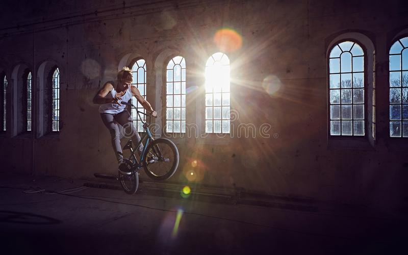 Download Эффектное выступление BMX и катание скачки в зале с солнечным светом Стоковое Изображение - изображение: 104843737