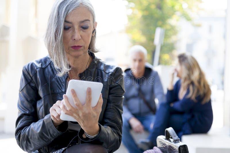 Элегантная дама советует с умным телефоном стоковая фотография rf