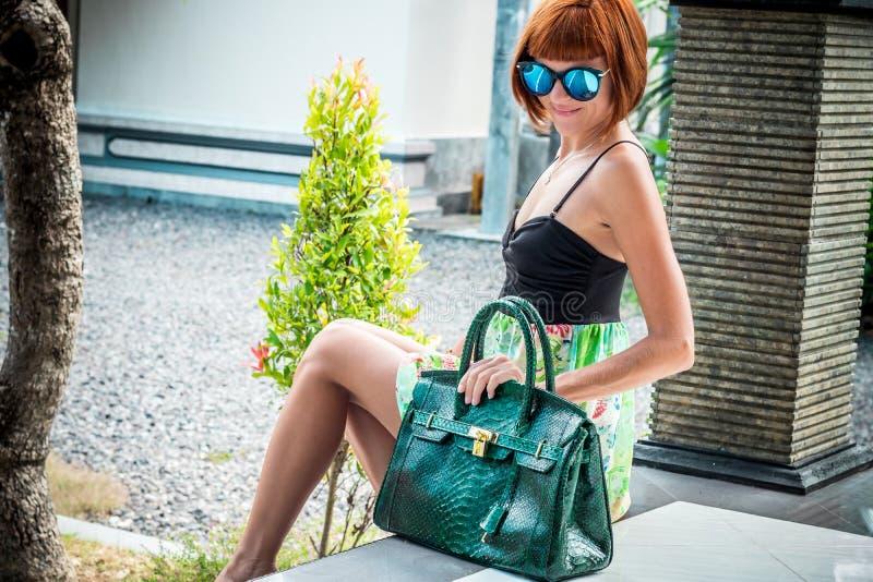 Элегантная дама с стильным коротким стилем причёсок и стекла держа роскошный питона кожи змейки кладут в мешки Остров Бали стоковые изображения