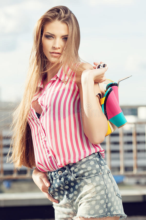 Элегантная латинская женщина держа ее ботинки стоковое фото rf