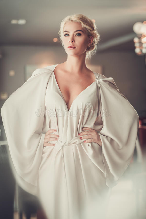 Элегантная белокурая дама в бежевом платье вечера в ресторане стоковые изображения rf