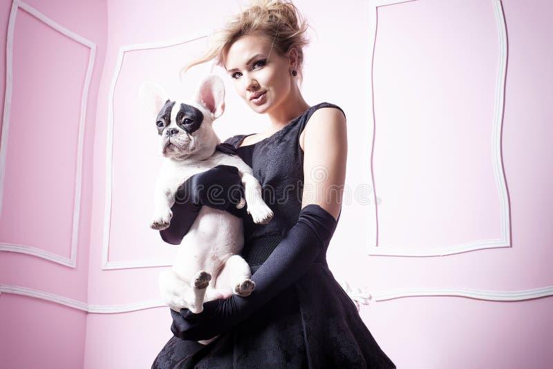 Элегантная белокурая женщина представляя с собакой мопса стоковая фотография rf