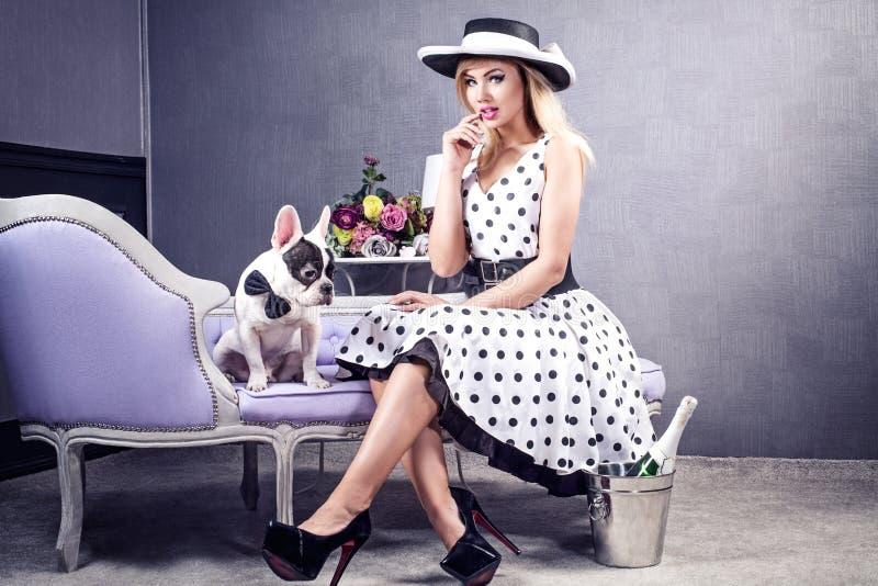 Элегантная белокурая женщина представляя с собакой мопса стоковое фото rf