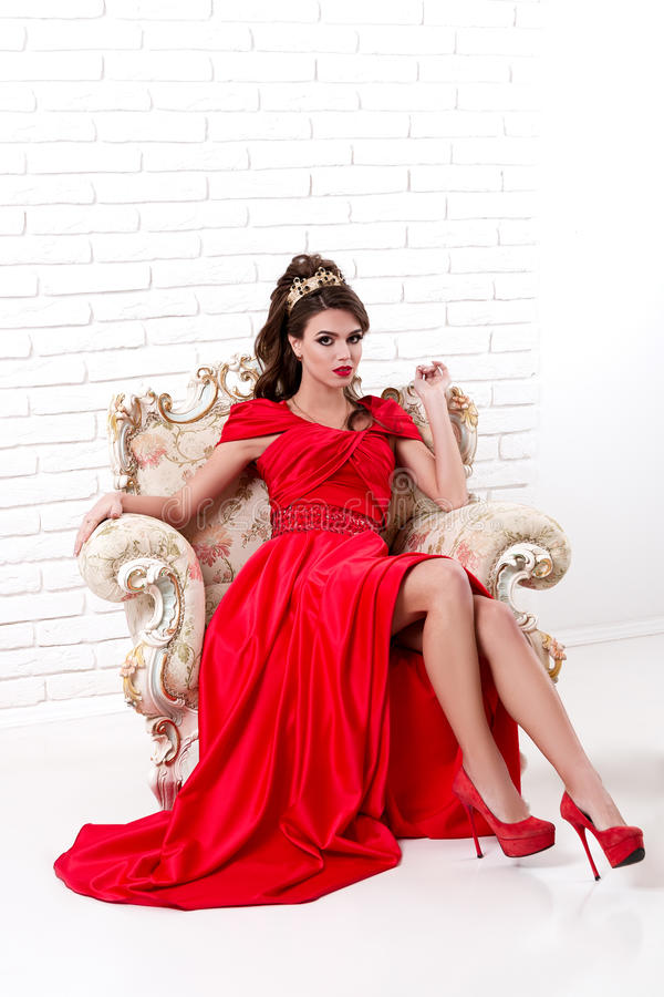 Элегантная женщина в длинном красном платье сидя на винтажном стуле внутри стоковое фото