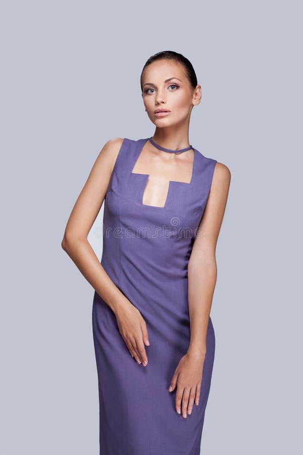 Элегантная женщина в модном стильном платье представляя в студии стоковая фотография