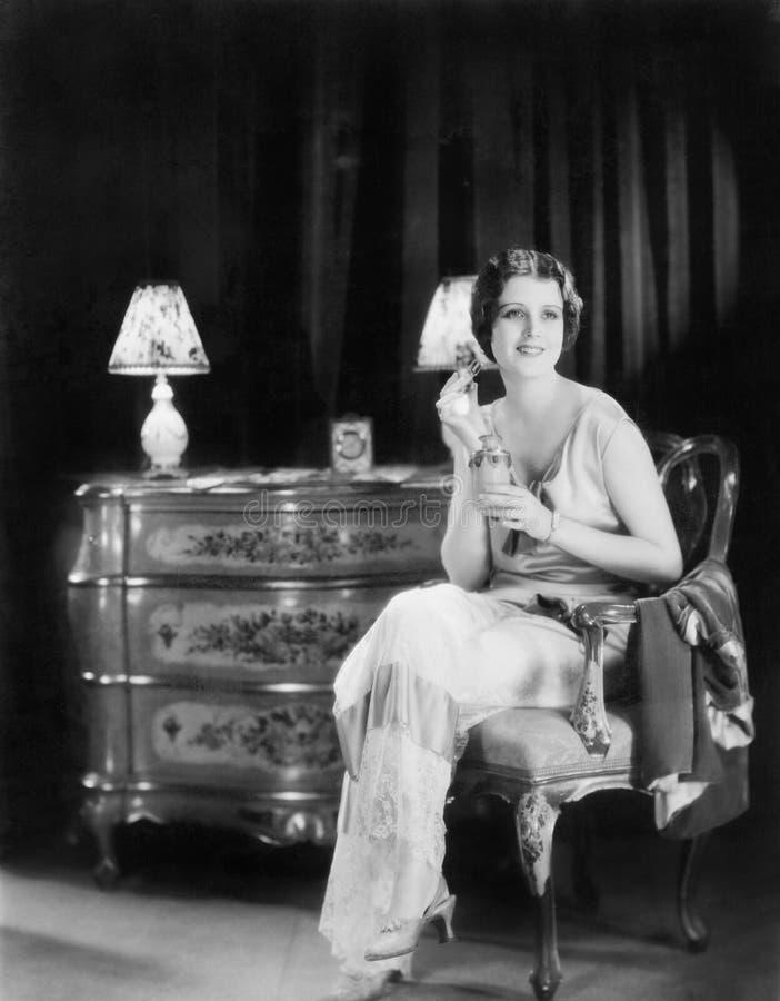 Элегантная женщина в платье вечера прикладывая дух к ее шеи (все показанные люди более длинные живущие и никакое имущество не сущ стоковая фотография rf