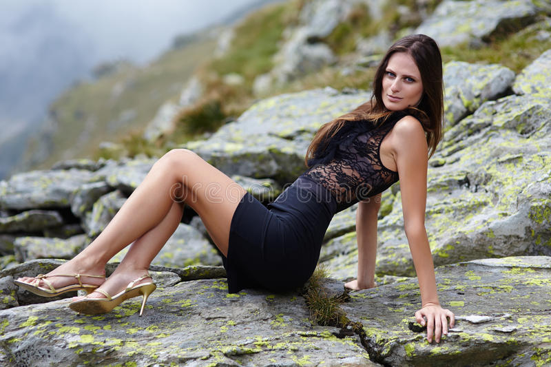 Элегантная женщина кладя на утесы горы стоковое изображение rf