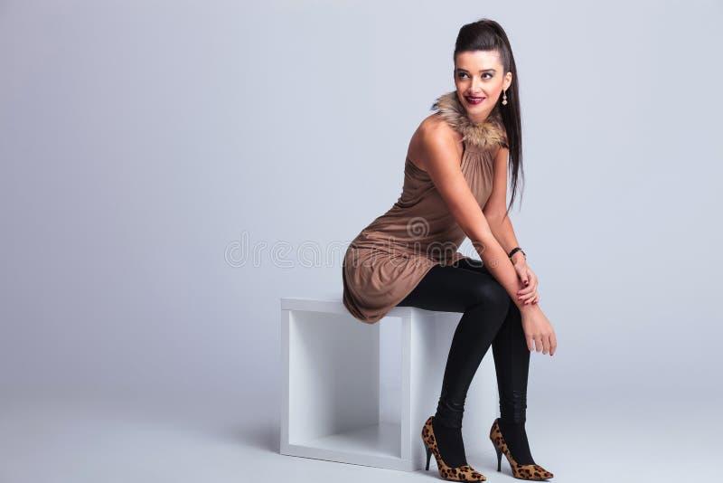 Элегантная женщина моды сидя на стуле пока усмехающся стоковое фото rf