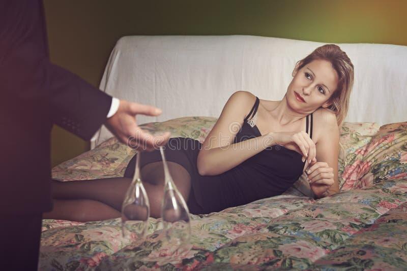Элегантная женщина на кровати готовой для того чтобы провозглашать стоковые изображения rf