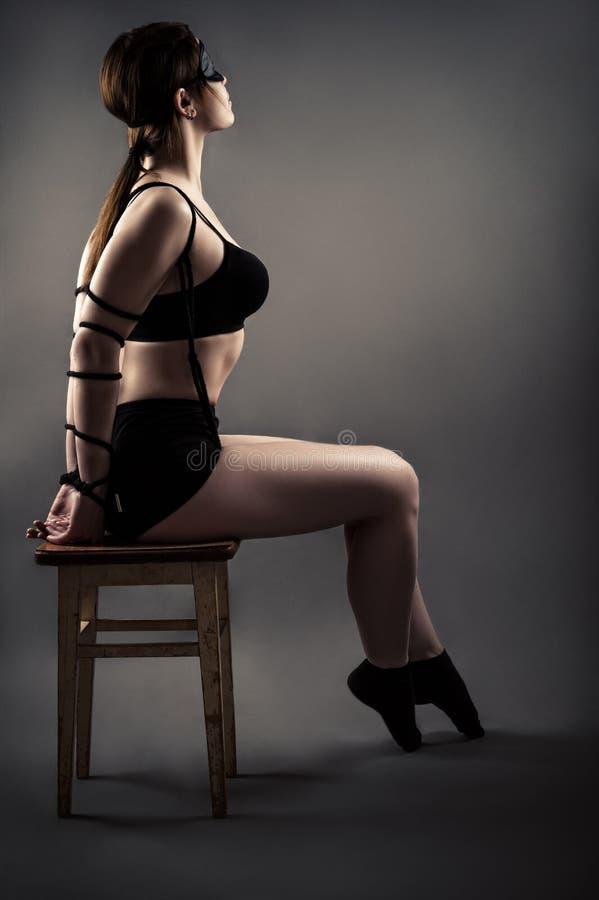 Элегантная женщина при связанные руки сидя на стуле с закрытыми глазами стоковые изображения rf