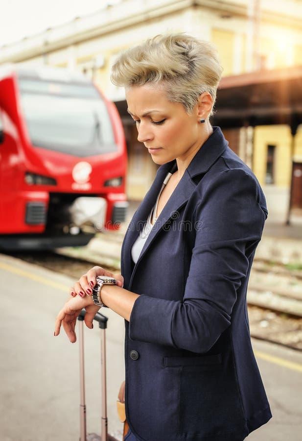 Элегантная женщина при чемодан ждать поезд на железнодорожном stati стоковая фотография rf