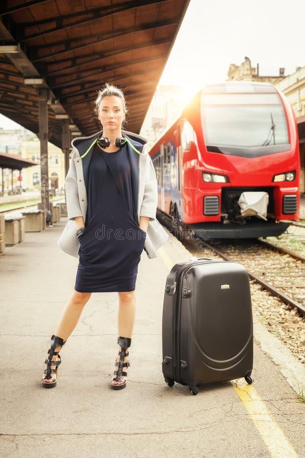 Элегантная женщина при чемодан представляя на железнодорожном вокзале стоковое фото rf