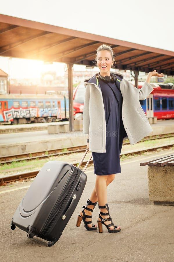 Элегантная женщина при чемодан представляя на железнодорожном вокзале стоковые фотографии rf