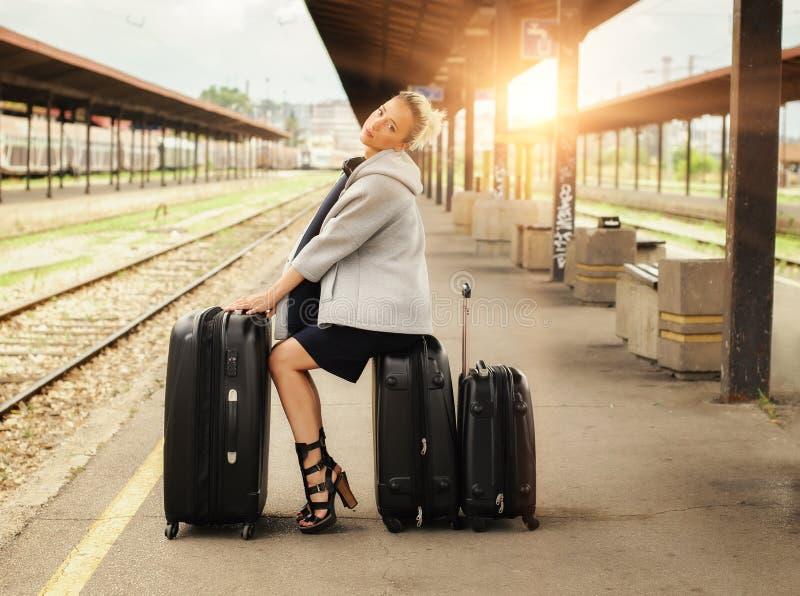 Элегантная женщина сидя на чемоданах и ждать поезд стоковые изображения rf
