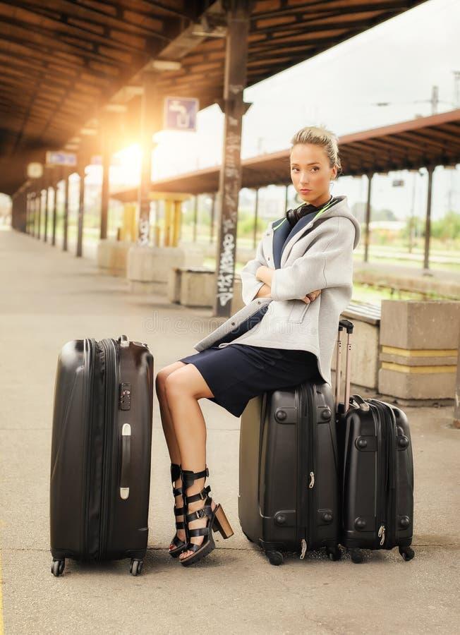 Элегантная женщина сидя на чемоданах и ждать поезд стоковые изображения