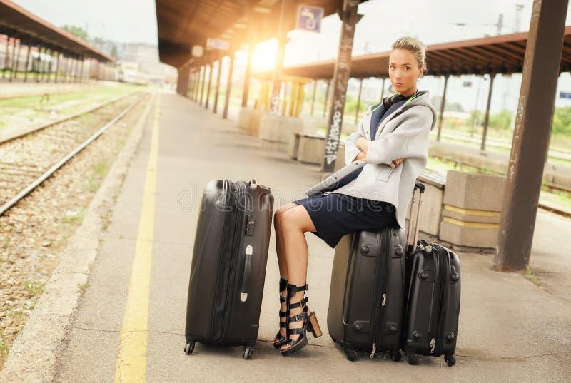 Элегантная женщина сидя на чемоданах и ждать поезд стоковое изображение rf