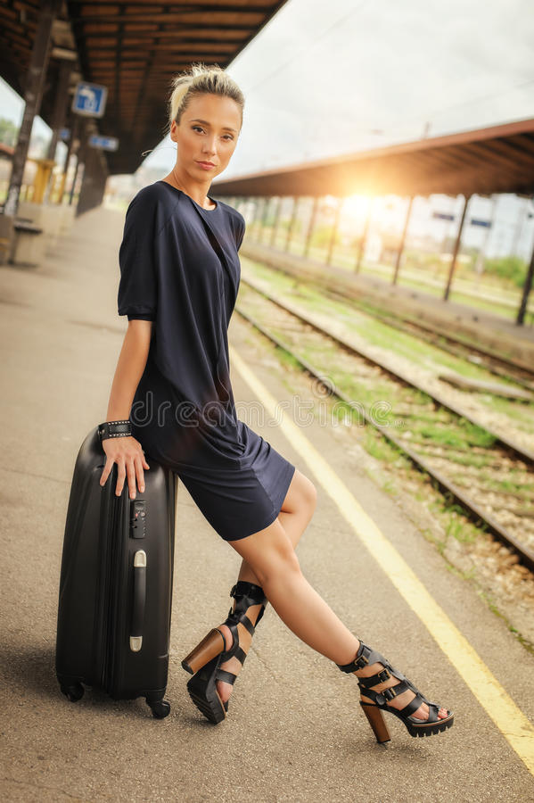 Элегантная женщина сидя на чемоданах на железнодорожном вокзале стоковые фото