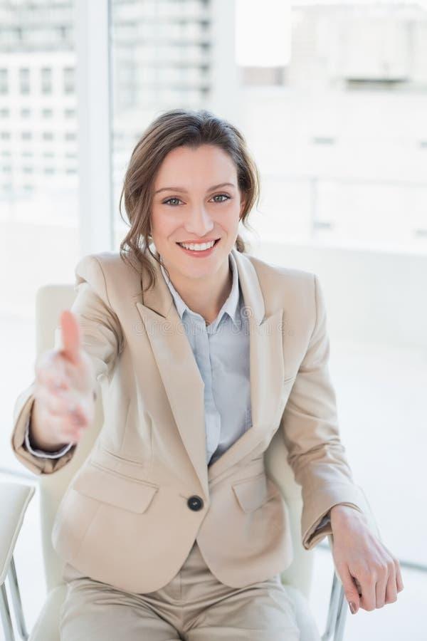 Элегантная коммерсантка предлагая рукопожатие в офисе стоковое изображение