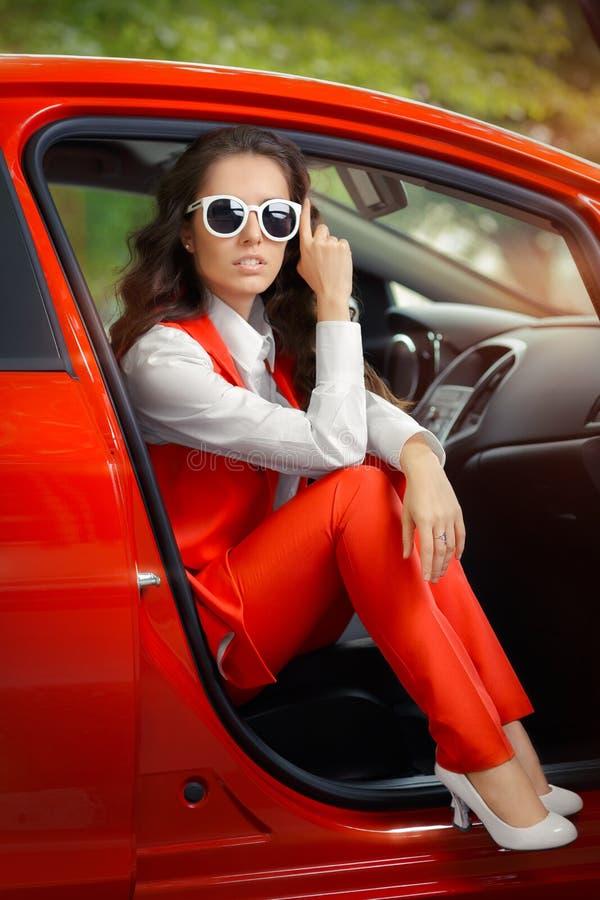 Элегантная красивая женщина в красном автомобиле стоковые изображения rf