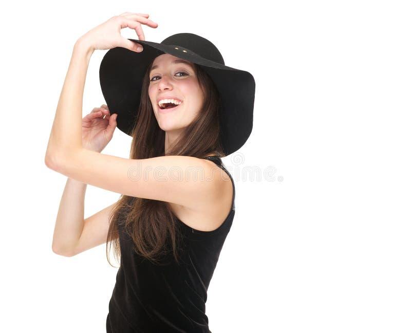 Элегантная молодая женщина усмехаясь с черной шляпой стоковое фото